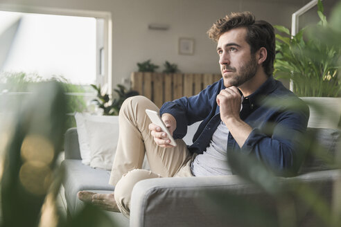 Young man sitting on couch at home, using smartphone - UUF17410