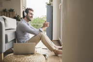 Young man sitting at home on floor, using laptop, listening music - UUF17422