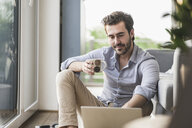 Young man sitting at home on floor, using laptop, drinking coffee - UUF17431