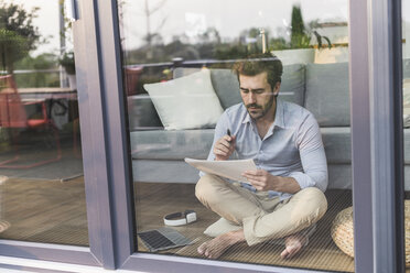 Young man sitting on ground, in front of window, taking notes - UUF17437