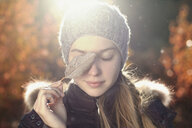 Caucasian teenage girl covering eye with leaf - BLEF02960