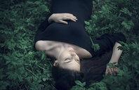 Caucasian woman wearing dress laying in green foliage - BLEF02963
