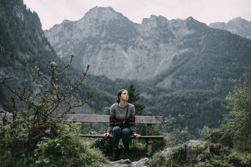 Caucasian woman sitting on bench in mountains - BLEF02981