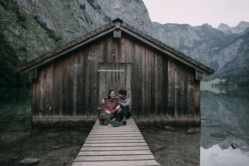 Caucasian couple sitting on dock at remote cabin - BLEF02987