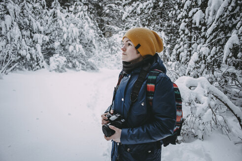 Caucasian woman holding camera in snowy forest - BLEF02993