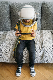 Boy playing video game on a games console, wearing space hat - JCMF00052