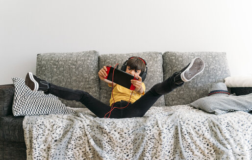 Kid lying on couch and playing with a video game console at home - JCMF00055