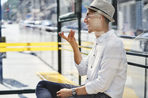 Side view of young man sitting at bus stop and talking on smartphone - BSZF01071