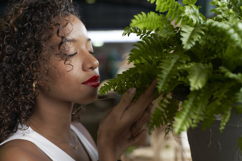 Young woman smelling fern - VEGF00137