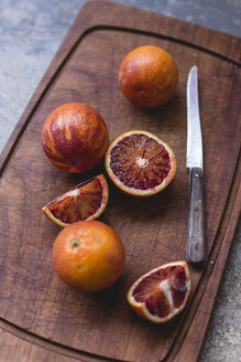 Whole and sliced blood oranges and a kitchen knife on wooden board - STBF00332