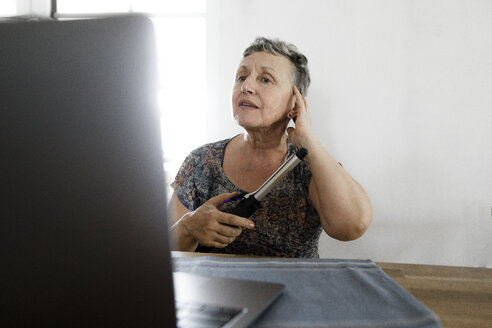 Senior woman sitting at table at home using laptop and doing her hair - KMKF00921