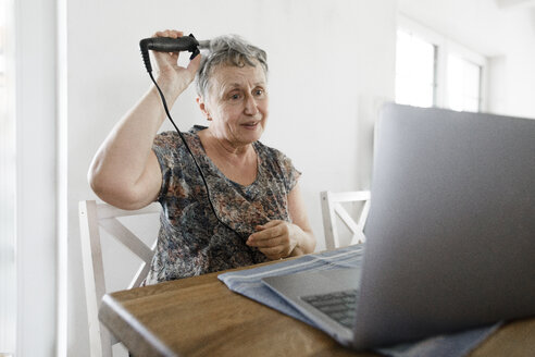 Senior woman sitting at table at home using laptop and doing her hair - KMKF00924