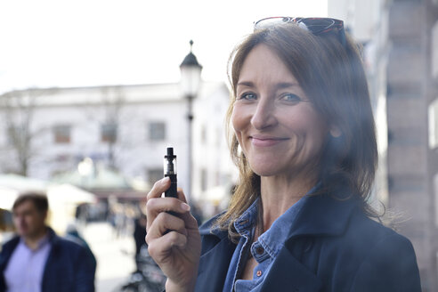 Mature woman smoking electronic cigarette in the city - ECPF00685
