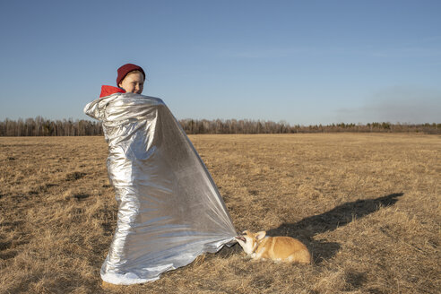 Boy wrapped up in superhero costume with dog in steppe landscape - VPIF01227