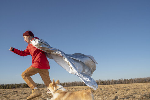 Boy dressed up as superhero running with dog in steppe landscape - VPIF01233