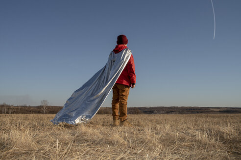 Rear view of boy dressed up as superhero looking at vapour trails in the sky - VPIF01242