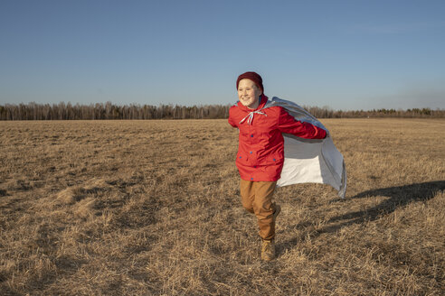Happy boy dressed up as superhero running in steppe landscape - VPIF01245