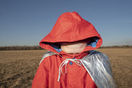 Boy dressed up as superhero in steppe landscape hiding his face in hood of his jacket - VPIF01251