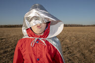 Hood of superhero costume covering boy's face in steppe landscape - VPIF01254