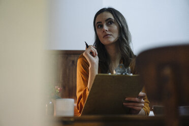 Young woman sitting at table with clipboard - KNSF05737