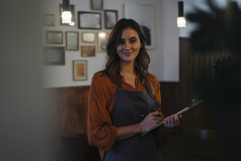 Portrait of smiling woman holding clipboard in restaurant - KNSF05743