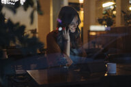 Young woman sitting at table in a restaurant with cell phone and tablet - KNSF05746