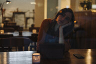 Serious young woman sitting at table in a restaurant using tablet - KNSF05749