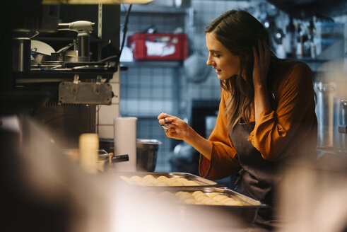 Young woman talking on cell phone in restaurant kitchen - KNSF05761