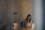 Young businesswoman working late at desk in office - KNSF05770