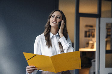 Young businesswoman holding folder talking on cell phone - KNSF05797