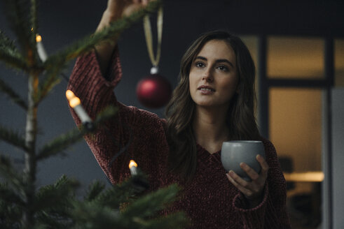Young woman decorating Christmas tree - KNSF05803