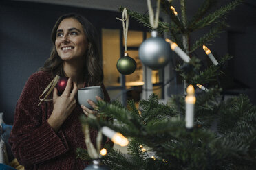 Smiling young woman decorating Christmas tree - KNSF05806