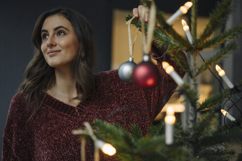 Young woman decorating Christmas tree looking away - KNSF05812