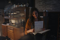 Smiling young woman looking into guestbook at restaurant counter - KNSF05821