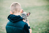 Boy carrying puppy outdoors - ISF21249