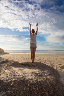 Woman standing on beach with hands raised practicing yoga, rear view, Cape Town, Western Cape, South Africa - ISF21267