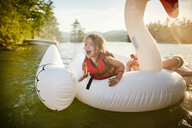 Girls playing on inflatable swan in lake - ISF21276