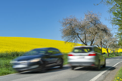 Germany, Mecklenburg-Western Pomerania, two cars passing by on country road - FRF00825