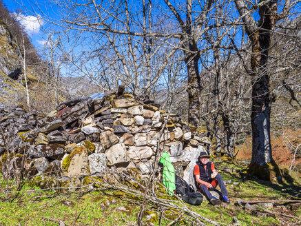 Spain, Asturia, Cantabrian Mountains, senior man on a hiking trip having a break - LAF02305