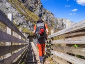 Spain, Asturia, Cantabrian Mountains, senior man on a hiking trip crossing a bridge - LAF02308