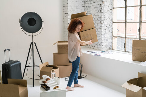 Mid adult woman moving into industrial style apartment, carrying boxes - CUF50505
