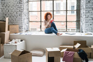 Mid adult woman moving into industrial style apartment, sitting on window ledge looking at book - CUF50523