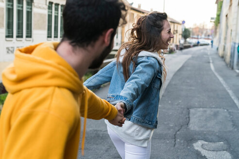 Happy young couple holding hands in city alleyway - CUF50544