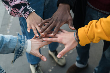 Four female and male young adult friends bringing hands together, close up of hands - CUF50547