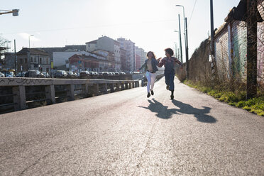 Two young women running along city road - CUF50553