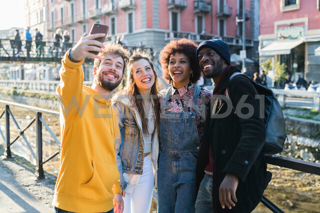 Four female and male young adult friends taking selfie on city canal waterfront - CUF50556