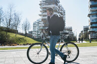 Man pushing bicycle and using smartphone, passing multi-storey building, Milan, Lombardia, Italy - CUF50583