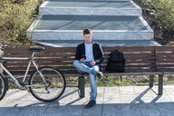 Man using smartphone on park bench, Milan, Lombardia, Italy - CUF50586