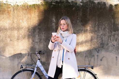 Female higher education student with bicycle looking at smartphone - CUF50601