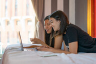 Friends using laptop in bed - CUF50622